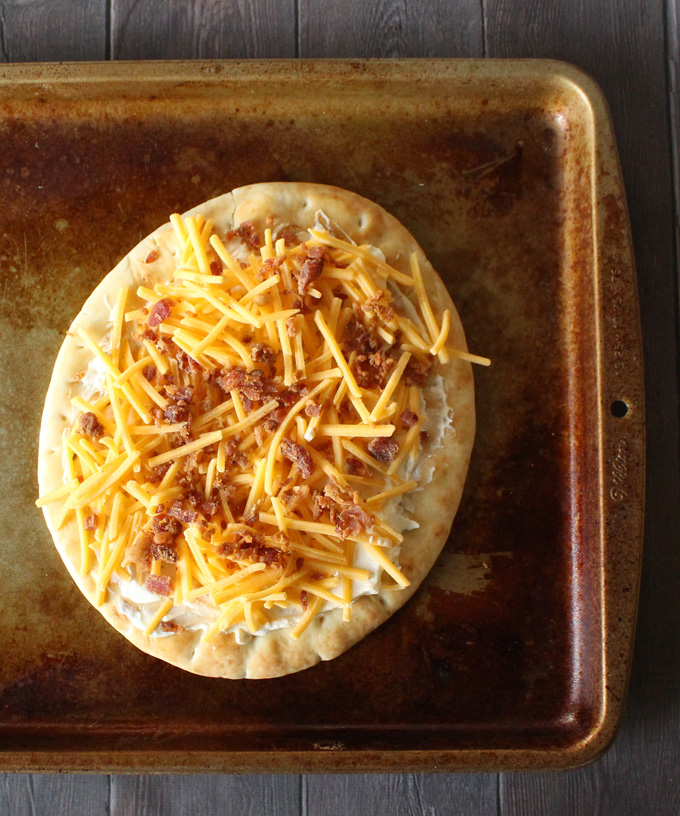 This recipe for Bacon Jalapeno Popper Pita Pizzas is perfect as a single-serving, kid friendly idea, & even works as an appetizer! Never complain about not having time to make dough again! View more recipes & lifestyle posts on Home in High Heels